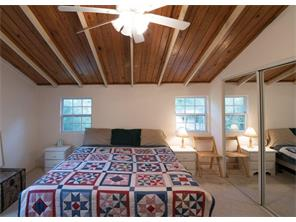 Spacious upstairs bedroom with closet and windows.  Cozy and warm with rustic beams and wood ceiling. 13x13