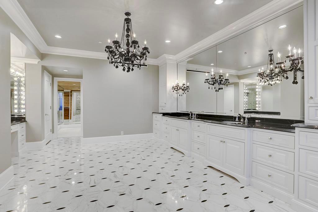 Custom designed and sensational.  Marble floors and counters.  Counter to ceiling mirrors. Separate sit down vanity area.  The door at the end leads to the closet.