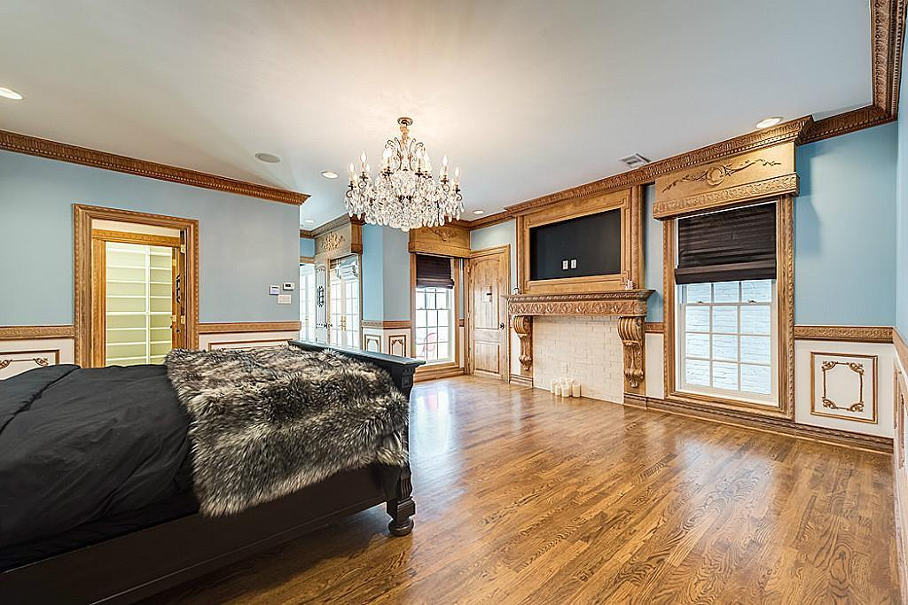 [Master Bedroom]A magnificent antique fireplace mantel with a framed space for a flat-screen television anchors one wall in the master bedroom.