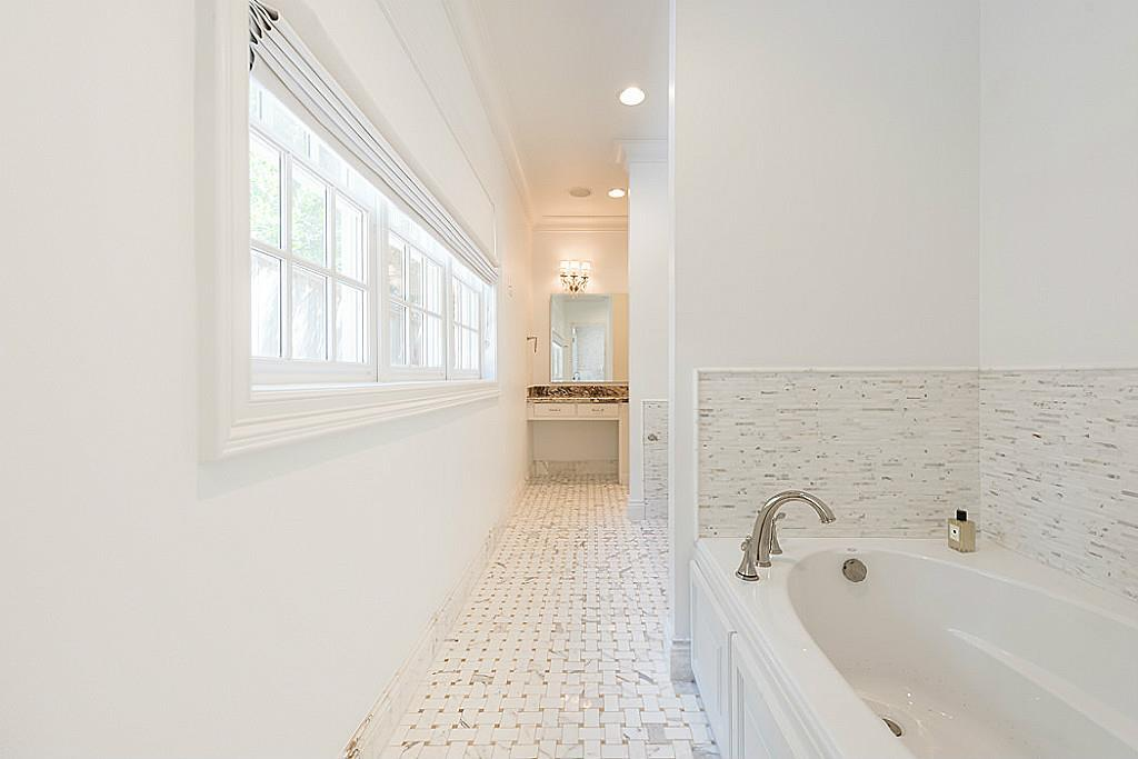 [Master Bathroom #1]View into master bathroom # 1 focuses on the air tub and basket- weave patterned marble-tiled floor.