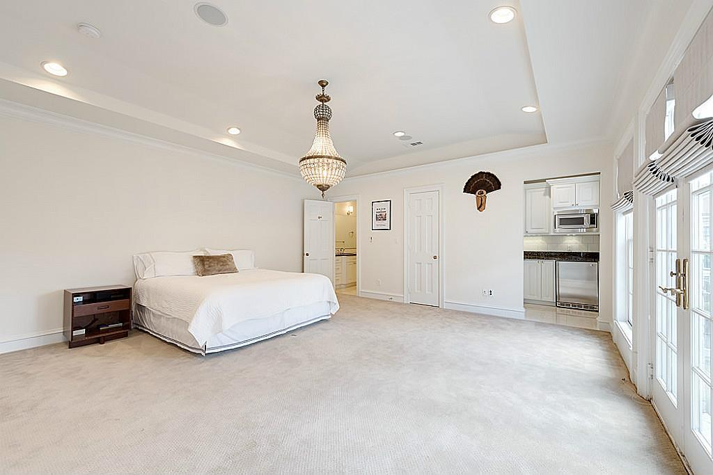 [Possible 2nd Master or Guest Suite 18x17]Positioned at the head of the return staircase and adjoining the media room, this large bedroom suite offers an attached marble-clad bathroom (left); custom-fitted closet, and a juice bar (shown at right).