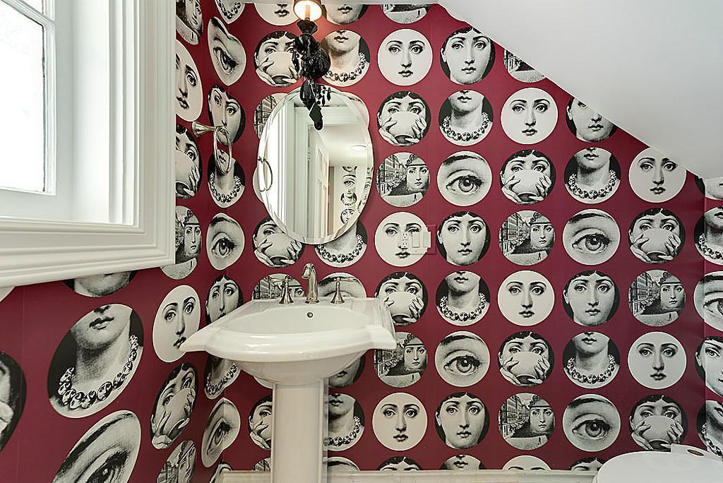 [Powder Bath]Charming powder bath located beneath the main staircase  has whimsical designer wallpaper and pedestal sink.