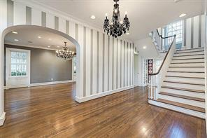 [Foyer]Past the gracefully-designed front door enhanced with sidelights and spider-web transom, the open, airy foyer divides the spacious formal rooms and transitions to French doors overlooking the rear patio and yard. Dining room is at left.