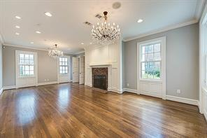 [Living Room 26x14]The living room features original hardwood floors, wainscot, paneling, and a brick fireplace.