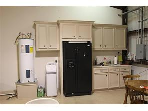 Cabinetry , refrigerator and sink in entertainment area.