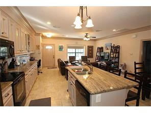 Granite Counters and Island  adorn the kitchen that is adjoined by the dining and living room in an open concept