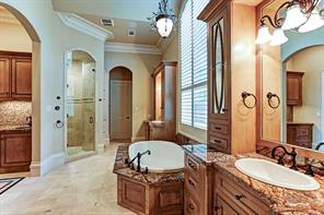 The master bath features a jetted tub, a frameless-glass and travertine shower, an under-counter refrigerator, a dishwasher drawer; and a microwave.