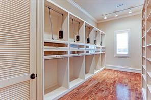 The first master closet has abundant storage with pull-downs and a built-ins. Behind the closet door is a stackable washer and dryer.