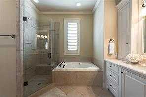 Fourth bedroom bath has a Jacuzzi tub with stone tile surround and Crema Marfil countertop.