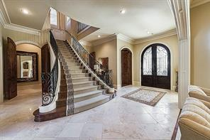 Foyer- Massive mahogany doors with seeded glass panels open into the light-filled, double-height foyer with polished limestone floor and a grand turning staircase.