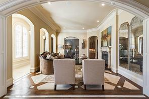The Living Room is enhanced with a stepped ceiling, alder-banded limestone floor, and a faux marble fireplace.