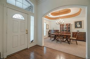 A beautiful archway opens towards the enchanting formal dinning room with chair rail and a recessed ceiling.