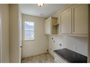 Laundry room has tons of storage cabinets and a folding area.