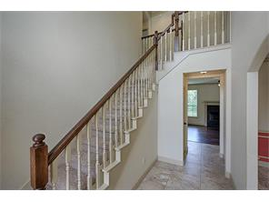 Graceful staircase located on the front of the house is one of two staircases to the second floor living space.