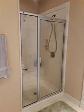 Oversized walk-in shower with a sitting bench.