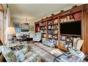 Handsome library with GumWood bookshelves with specialty lighting, architecturally designed passage into the dining room on the right.