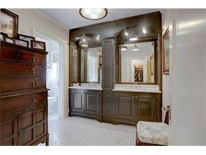 Double sinks in master bath, all woodwork was handpainted in renovation.  Doorway to the left into shower area.