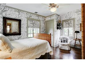 Secondary bedroom with matching wallpaper and draperies.  Cozy and quaint.