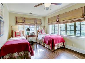 Secondary bedroom wtih burlap shades, hardwood floors and tucked away for ultimate privacy.