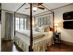 Guest house bedroom, toile curtains, hardwood floors and ceiling fan.