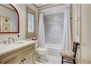 Guest house bath with tub/shower and vanity.