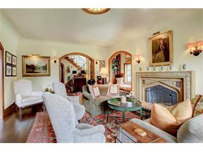 Living room with original wood burning fireplace with stunning mantle and old world plaster walls.  Many original lighting fixtures.