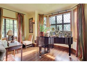 Far end of the living room turned music area in this elegant bay window with original diamond shaped leaded glass windows.  Door leading to the side yard on the far right side.