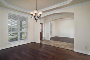Formal Dining Room includes Tray Ceiling, Elegant Arched Doorways, Wood Flooring, Crown Molding, and designer lighting.
