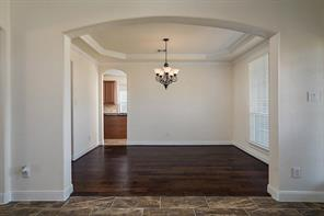 Elegant Arched doorway into Formal Dining Room with Tray Ceiling and Crown Molding.