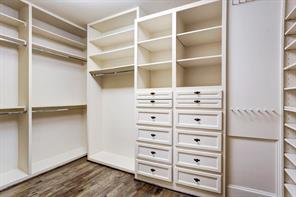 One of the two master closets featuring plenty of storage and hardwood flooring