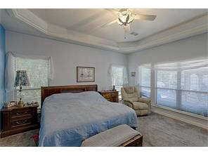 Large wall of windows in the Master Bedroom overlooking the pool.