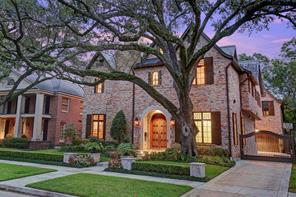 Beautiful treed lot with brick exterior, timeless slate roof and iron security gate leading to 2 car garage with additional parking.