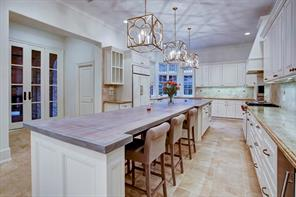Another view of kitchen.  There is a subzero refrigerator freezer, grantite counters and marble backsplash.  There is access to a covered loggia with fireplace.