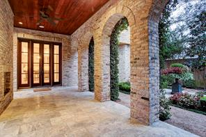 Downstairs covered loggia with fireplace is accessible from kitchen and has views of yard and gardens.