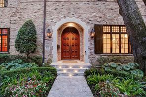 Beautiful covered entry with double custom detailed wood doors.