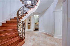 Dramatic foyer with stone floors, wood and wrought iron staircase has arched entries leading to dining room and library.