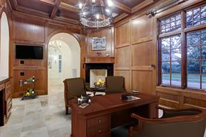 Another view of the library with granite fireplace with wood mantle with views of the grand entry and dining room.