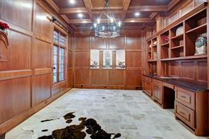 Very handsome wood paneled library with wall of builtins and limestone floors.  There is a granite fireplace not shown in this photo.