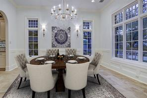 Light and bright dining area with limestone floors and crystal chandelier and exterior views. It is to the right of the foyer and has butler pantry adjacent