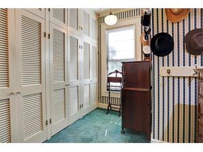 MASTER CLOSET AND DRESSING ROOM - charming patterned wallpaper, carpeting, wall of closet and storage space behind louvered doors