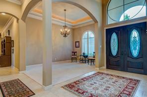 A formal dining room (12  x 16 ) that has another gorgeous hanging chandelier, recessed rope lighted tray ceiling and architectural features such as the arched window and soft arches to define the dining room space.