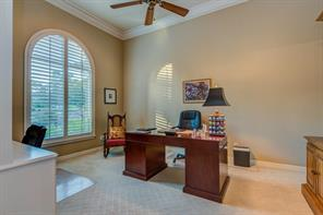 An executive sized study (12 x 14 ft. ) has a large built - in desk, cabinets and bookshelves to the left.  High ceilings in the home are 10  to 12 ft. and many rooms have these great plantation shutters.