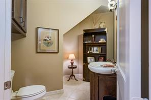 A darling guest bath has a cabinet over the commode, an oval sink with storage below and room for a special display cabinet with shelving for perfumes, towels, curios, etc.