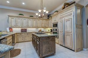 Beautiful custom faux painted cabinets and side by side refrigerator with contrasting painted island are special features of this kitchen.  The cook top is gas and the countertops are a gorgeous granite.  There is a walk-in pantry to the right.
