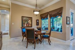 This breakfast table area is perfect for watching the golfers in the morning . Notice the extra wide crown molding and soft neutral paint wall colors. The hallway leads to the dining, foyer and living room.
