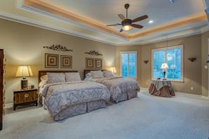 "A ""Dream"" Master Bedroom with room for 2 Queen size beds and still plenty of space for conversation or reading area. Notice the Tray ceiling with rope lighting, bayed windows, lighted ceiling fan, plantation shutters and wide crown molding ."