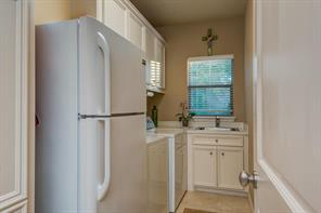 In this utility room there is a broom closet to the left, cabinets overhead, a sink under the window and room for a refrigerator.