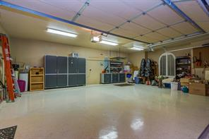 This large 3 car garage has large metal cabinets and a workbench that can stay with the house.  The floor is Epoxy which is easy to clean, there is ample lighting overhead, a side entry door and pull down attic stairs.