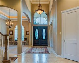 The foyer has a 20 ft. ceiling with a stunning chandelier and a large arched window over the double oval cut glass entry doors.  The  study is to the right and the formal dining is to the left.