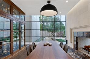 The Dining Area is bounded by the wine wall and double sided carved marble fireplace with commanding views of the koi ponds to the north and limestone edged pool to the south.